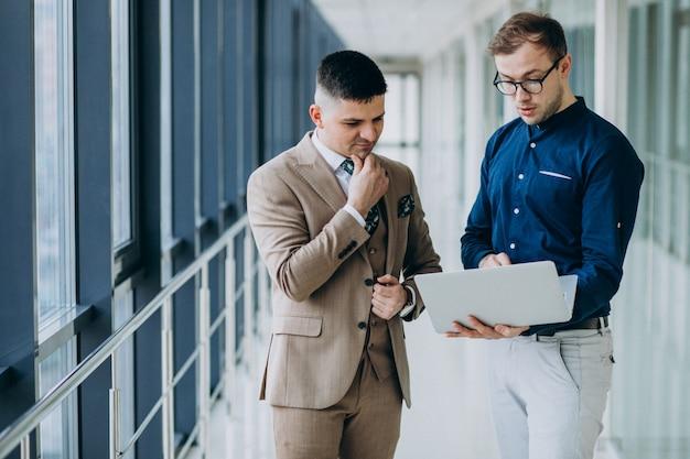 ノートパソコンで立っているオフィスで2人の男性の同僚 無料写真