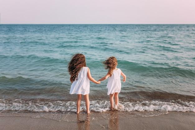 白いドレスの2人の女の子が海の泡でビーチに立っています。 Premium写真