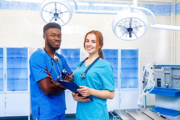 手術室に立っている病院で2人の若い医師の多民族チーム Premium写真