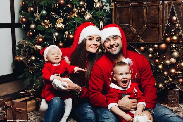 クリスマスツリーで楽しんでいる2人の愛らしい子供と幸せな家族 Premium写真
