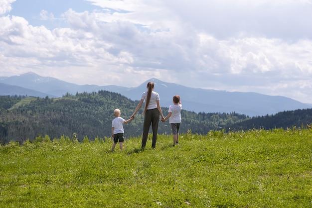 母と2人の幼い息子が緑の野原に手を取り合って立っています。 Premium写真