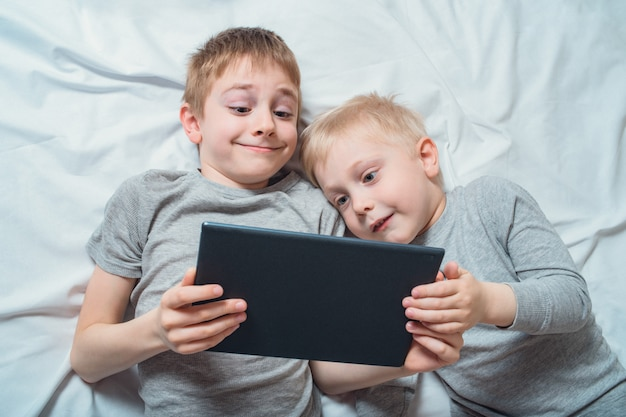 ベッドで横になっていると、タブレットで何かを見ている2人の男の子。ガジェットレジャー Premium写真
