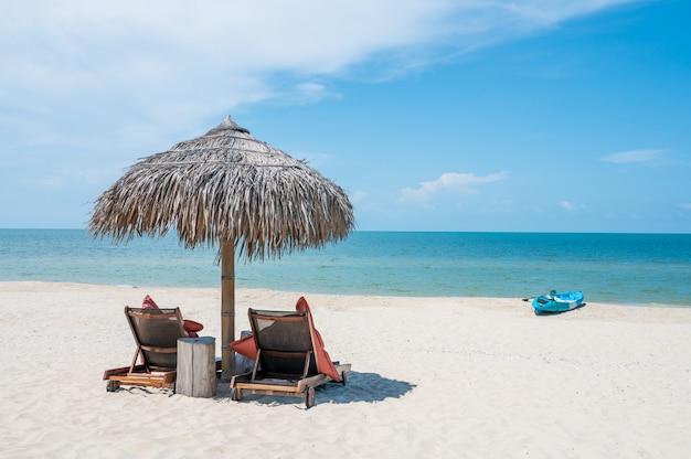 トロピカルビーチのパラソルの下で2つの椅子 Premium写真