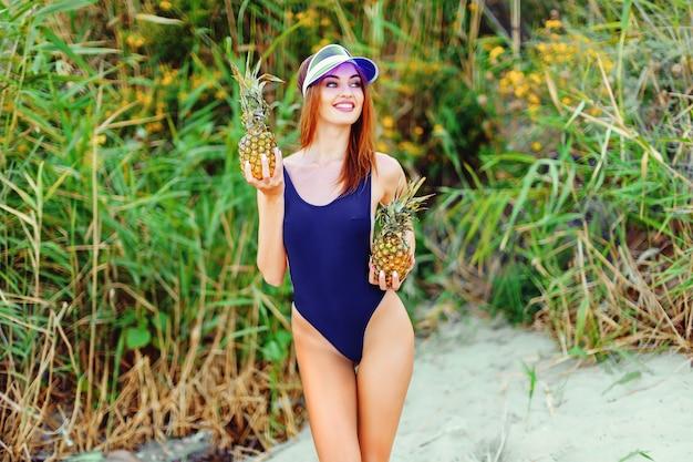 2つのパイナップルを保持している熱帯の島の海岸のモノキニの女の子モデル Premium写真