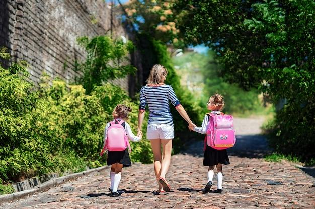 親と小学校の2人の生徒が手をつないで行きます。女性と少女の背中の後ろにバックパック。レッスンの始まり。秋の初日 Premium写真