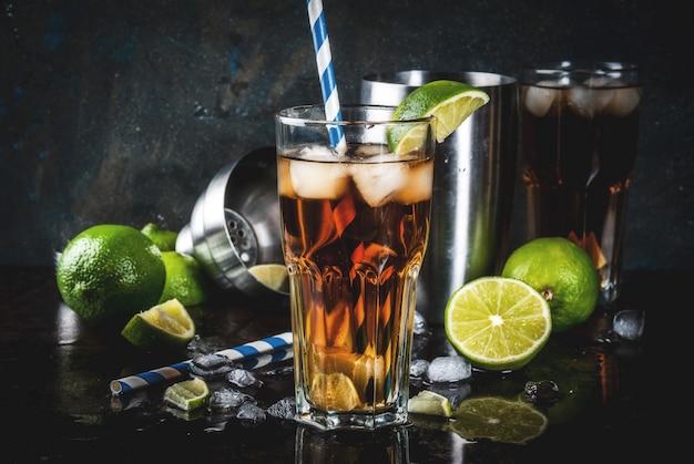 キューバリブレ、ロングアイランドまたはアイスティーカクテル、強いアルコール、コーラ、ライム、アイス、2杯のグラス、ダーク Premium写真