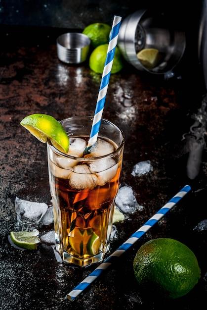 キューバリブレ、ロングアイランドまたはアイスティーカクテル、強いアルコール、コーラ、ライム、氷、2枚のガラス、暗い表面のコピースペース Premium写真