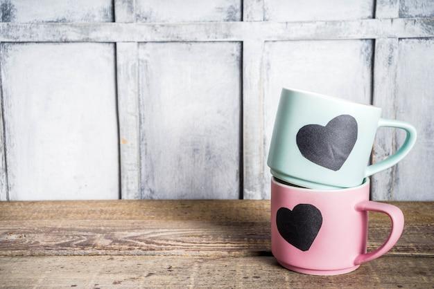 黒板の心を持つ2つのかわいいティーカップ Premium写真