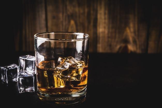 アイスキューブと暗い木製のテーブルに2つのウイスキーショットグラス、 Premium写真