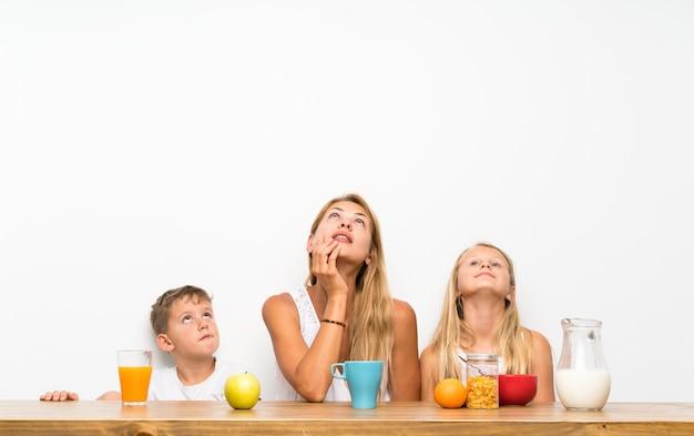 見上げる朝食を持つ彼女の2人の子供を持つ母 Premium写真