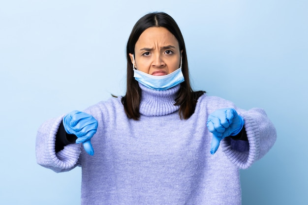 2つの手で親指を示す青い壁の上のマスクと手袋で保護する若いブルネット混血女性 Premium写真