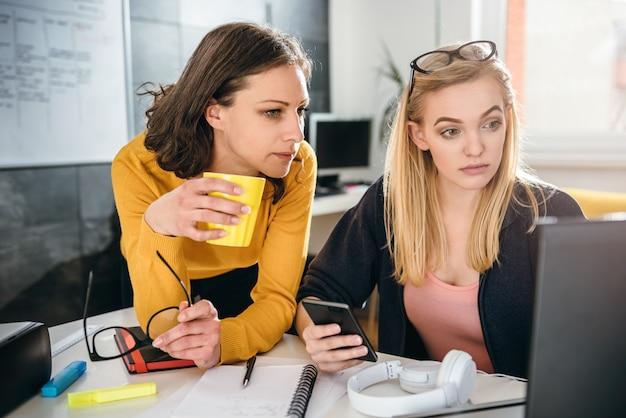 オフィスで一緒に働く2つのビジネス女性 Premium写真