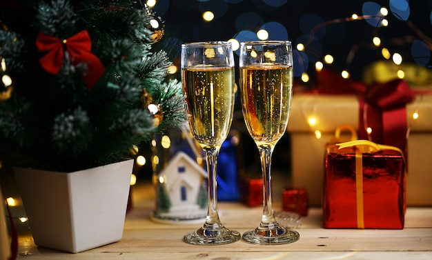 クリスマスツリーのそばのシャンパンの2つのガラス Premium写真