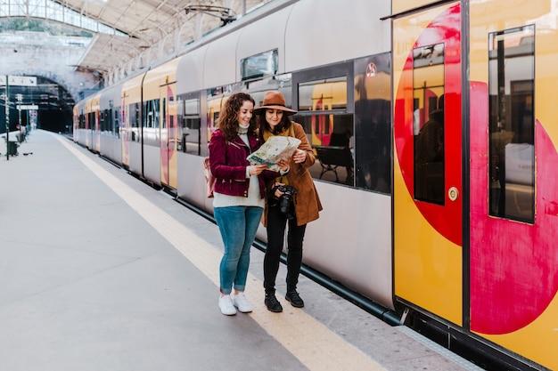 電車に乗って旅行を待っている駅で2人の女性の友人。地図を読んで楽しんで。 Premium写真