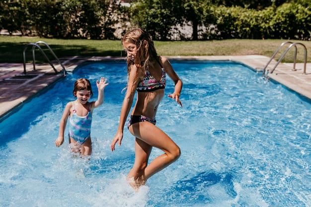 遊んで、実行して、屋外で楽しんでプールで2人の美しい姉妹の子供。夏とライフスタイルのコンセプト Premium写真