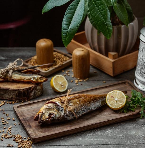 レモンとパセリを木の板で提供する2つの乾燥スモーク魚 無料写真