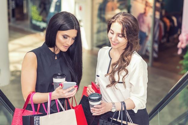 スマートフォンとショッピングセンターのショッピングバッグを持つ2人の美しい女性。 Premium写真