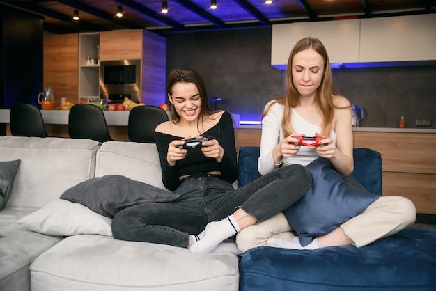 隔離中に自宅でコンピュータゲームをすることに情熱を傾ける2人のガールフレンド。世界パンデミックの家の隔離。余暇を過ごす時間を楽しんでください。 Premium写真