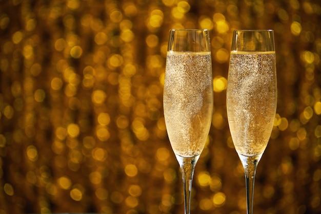 背景のボケ味の黄金のシャンパンを2杯 Premium写真