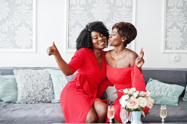赤い美容ドレスの2つのファッションアフリカ系アメリカ人モデル、ソファに座って一緒に楽しんでイブニングドレスをポーズセクシーな梨花。 Premium写真