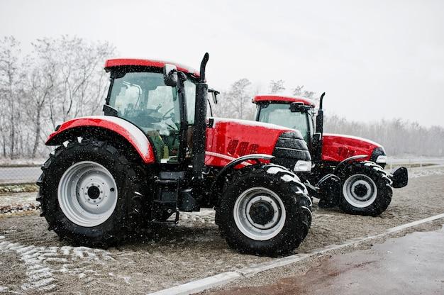 2つの新しい赤いトラクターが雪の天気で滞在します。 Premium写真