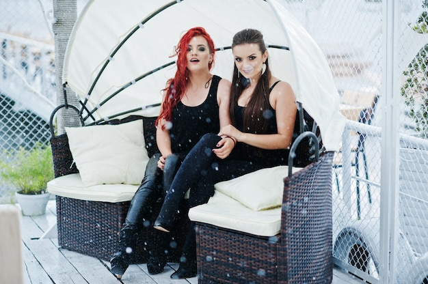 雨でソファに座っている2人の女の子 Premium写真