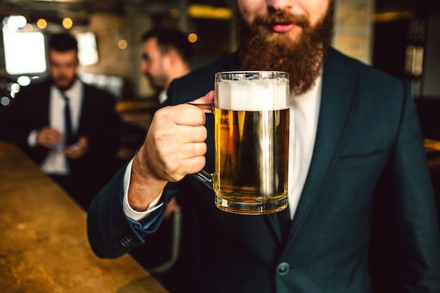 スーツのひげを生やした男のビューをカットビールジョッキを保持します。他の2人のオフィスワーカーは後ろに座っています。 Premium写真