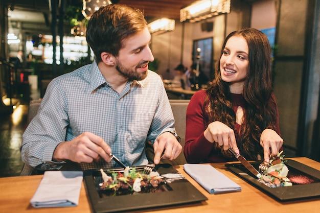 2人の素敵な人がレストランに座ってサラダを食べています。また、彼らはお互いを見て笑っています。 Premium写真