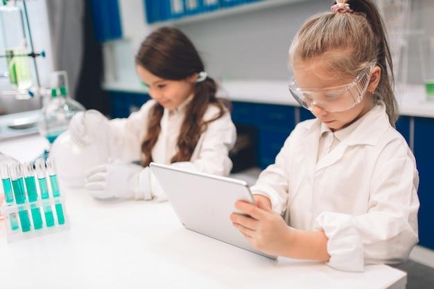 学校の実験室で化学を学ぶ白衣の2人の小さな子供。実験室や化学キャビネットで実験を行う保護メガネの若い科学者。タブレットでの作業。 Premium写真
