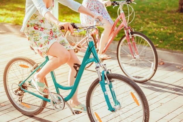 公園で自転車を持つ2人の若い女の子 無料写真