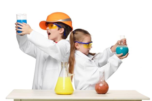 化学レッスンで2人のかわいい子供たちが実験を行う 無料写真
