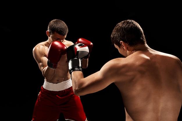 黒い壁にボクシング2つのプロのボクサー 無料写真