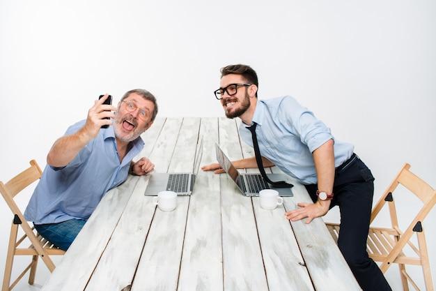 2人の同僚がオフィスに座っている自分に写真を撮る 無料写真