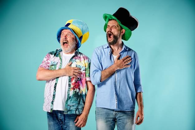 青で国歌を歌う2人のフットボールのファン 無料写真
