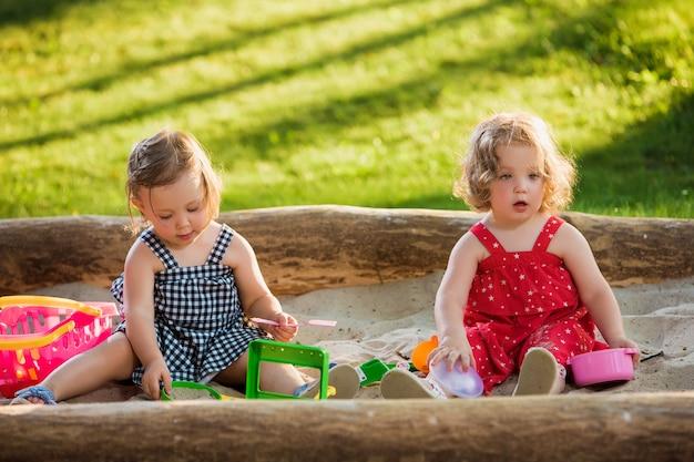 砂でおもちゃを遊んでいる2人の小さな女の赤ちゃん 無料写真