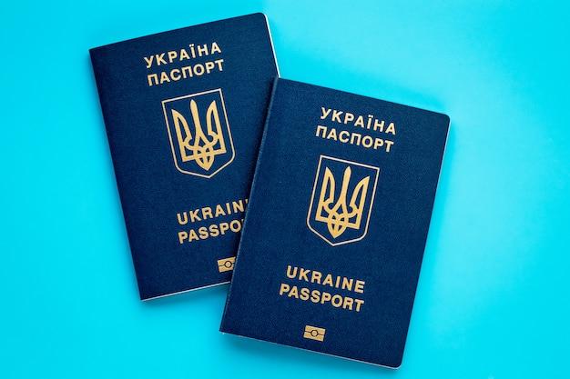青色の背景に2つのウクライナの生体認証パスポート。休暇の概念を計画しています。国際パスポート。 Premium写真