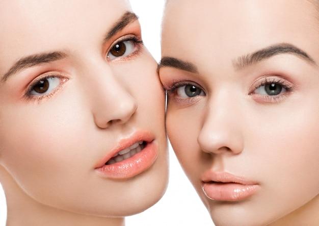白い背景の上の自然の美しさの化粧品で2つの美しいモデル Premium写真