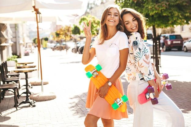 笑顔の通りにペニースケートボードに座っている2人の若い友人 無料写真