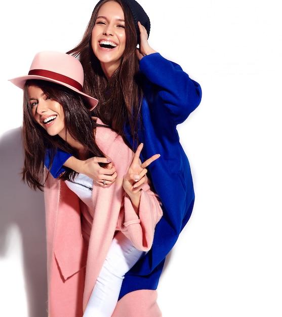 Фасонируйте портрет 2 усмехаясь моделей женщин брюнет в вскользь пальто битника лета изолированном на белизне. девушки держат друг друга на спине Бесплатные Фотографии