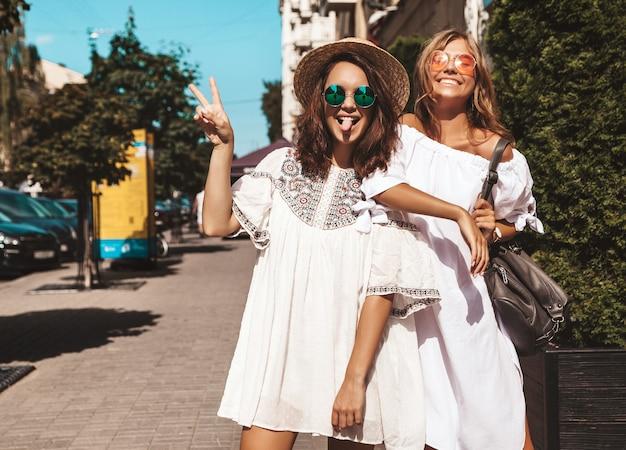 夏の晴れた日に2人の若いスタイリッシュなヒッピーブルネットとブロンドの女性のファッションの肖像画。白い流行に敏感な服を着たモデル。梨花のポーズ 無料写真