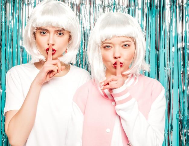 白いかつらと赤い唇の2人の若いセクシーな流行に敏感な女の子。夏服で美しいトレンディな女性。スタジオで青い銀の光沢のある見掛け倒しの背景にポーズをとるモデル。 無料写真