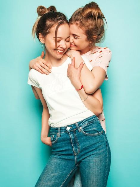 トレンディな夏のヒップスタージーンズの服で2人の若い美しいブロンド笑顔流行に敏感な女の子。水色の壁に近いポーズのセクシーな屈託のない女性。楽しいトレンディでポジティブなモデル 無料写真