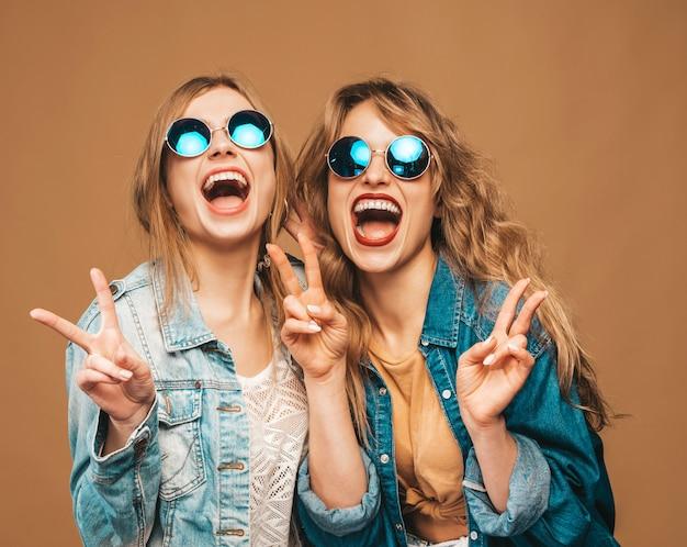 トレンディな夏服とサングラスで2人の若い美しい笑顔の女の子。セクシーな屈託のない女性がポーズします。ポジティブな叫びモデル 無料写真