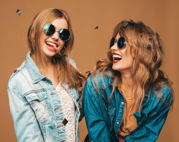 トレンディな夏服とサングラスで2人の若い美しい笑顔の女の子。セクシーな屈託のない女性がポーズします。紙吹雪の下で肯定的な悲鳴モデル 無料写真
