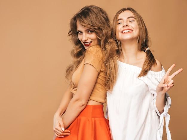 トレンディな夏服の2人の若い美しい笑顔の女の子。セクシーな屈託のない女性がポーズします。ピースサインを示す肯定的なモデル 無料写真