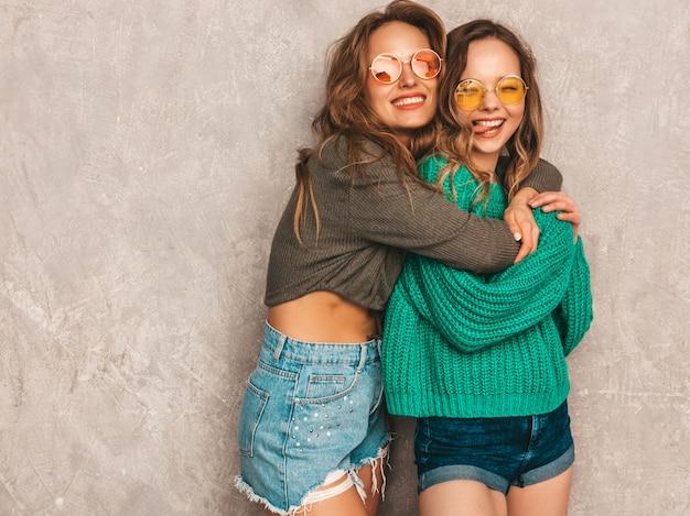 トレンディな夏服で2人の若い美しい笑顔の豪華な女の子。セクシーな屈託のない女性がポーズします。ラウンドサングラスを楽しんでいる肯定的なモデル 無料写真