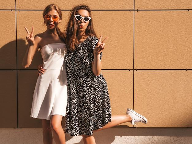 トレンディな夏の2人の若い美しい笑顔流行に敏感な女の子をドレスアップします。 無料写真