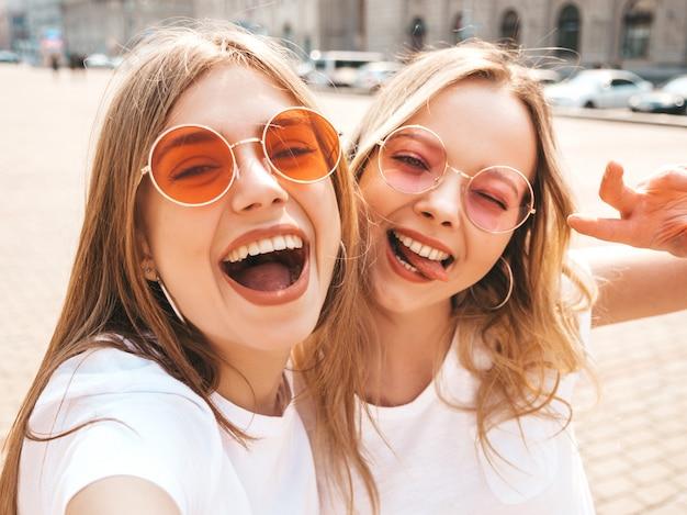2 молодых усмехаясь женщины битника белокурых в одеждах футболки лета белых. девушки фотографируют автопортрет селфи на смартфоне. модели позируют на улице. женщина показывает знак мира и язык Бесплатные Фотографии