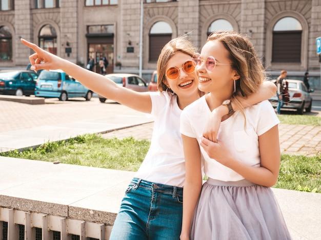 白い流行に敏感な服のポーズで夏の晴れた日に2つの若いスタイリッシュなヒッピーブルネットとブロンドの女性モデルのファッションの肖像画 無料写真