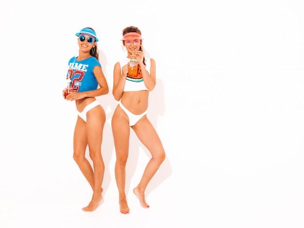 白い夏のパンツとトピックの2人の美しい笑顔のセクシーな女性。サングラス、透明なバイザーキャップのトレンディな女の子。発狂。面白いモデルが分離されました。新鮮なカクテルスムージードリンクを飲む 無料写真